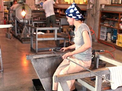 富山ガラス工房で制作に取り組むスタッフ。手前右の4点は富山大和に展示され、同左の3点は市ガラス美術館のショップに並べられる