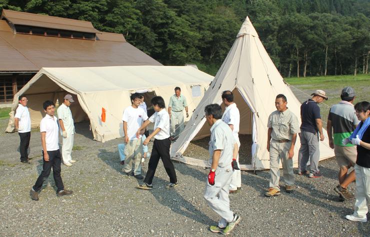 テントの設置練習に取り組む実行委メンバーら=利賀国際キャンプ場
