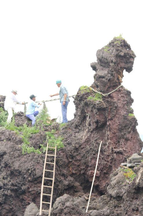 弁天岩にしめ縄を取り付ける「里の会」の会員=佐渡市椿尾