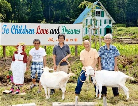 「風月森の駅」のメンバーと飼育されているヤギ。3月には赤毛のアンの家をイメージしたヤギの飼育舎(右後方)を建てた=越前市轟井町