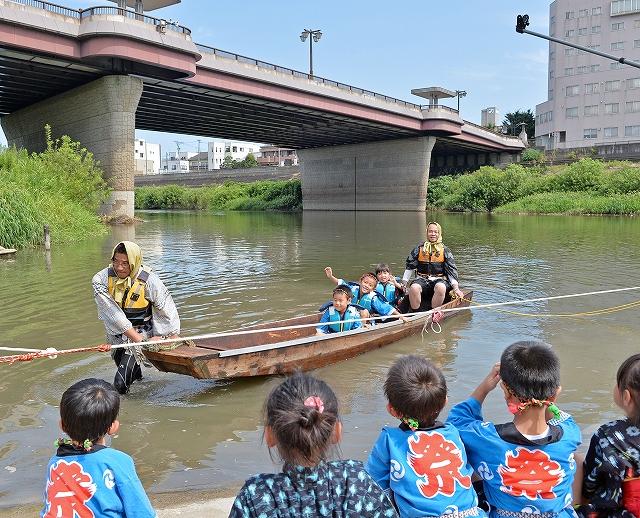 足羽川の新たな風物にしようと再現された繰舟を楽しむ園児=7日、福井市の九十九橋上流