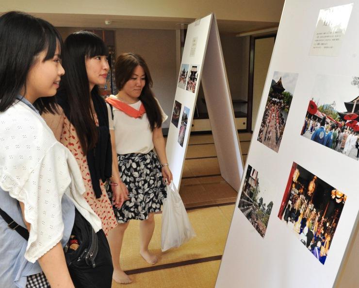 御開帳の諸行事を撮影した写真を見る女性たち