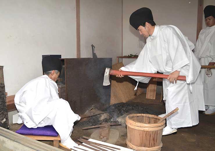 朱塗りの神斧を火にかざして清める山作り衆(代表撮影)