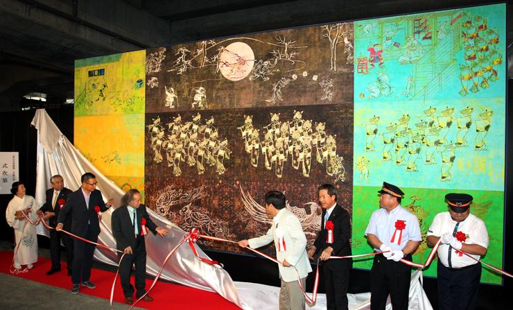 作者の宮廻氏(左から4人目)ら関係者が除幕した大型壁画=JR富山駅東西自由通路