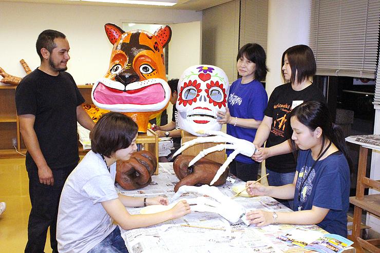 ピオさん(左)の指導で完成が近づく巨大人形の頭部。手前は骸骨の手=南砺市福野文化創造センター