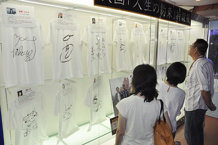 出演者のサイン入りTシャツに見入る来場者=道の駅新湊