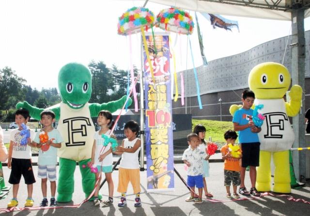 特別展入場者が10万人を突破し、くす玉を割って祝う子どもたち=16日、福井県立恐竜博物館
