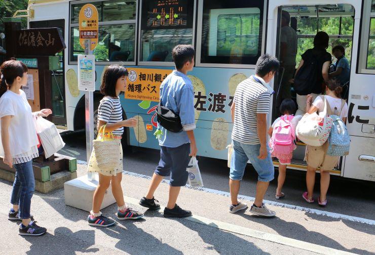 佐渡金山の停留所で観光循環バスに乗り込む観光客ら=16日、佐渡市