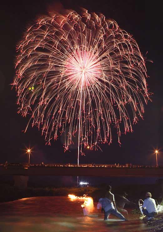 灯籠が流される天竜川の上空を彩る花火=18日午後8時29分、高森町