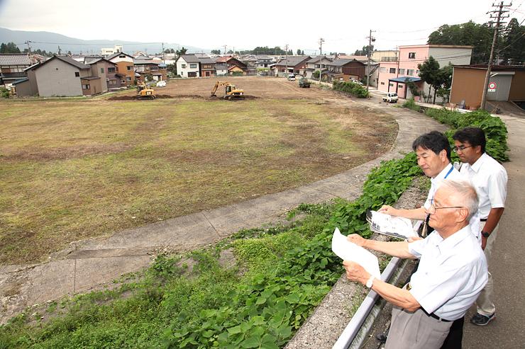 新たな有料駐車場にする工場跡地で図面を手に整備の進み具合を確認する岩田会長(右手前)ら=南砺市城端