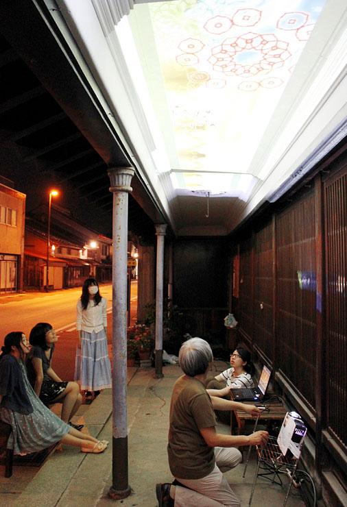 菅野家の軒下の天井部分に映像を試験投影する学生ら=高岡市木舟町