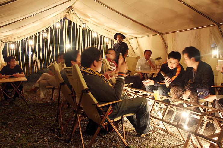 温かな光に包まれた大型テントの中で飲食を楽しむ来場者=利賀国際キャンプ場