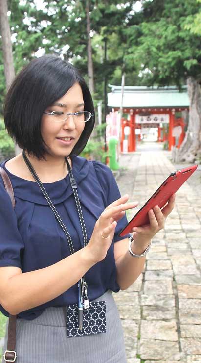 上田市下之郷の生島足島神社でイングレスの画面を見る山本さん