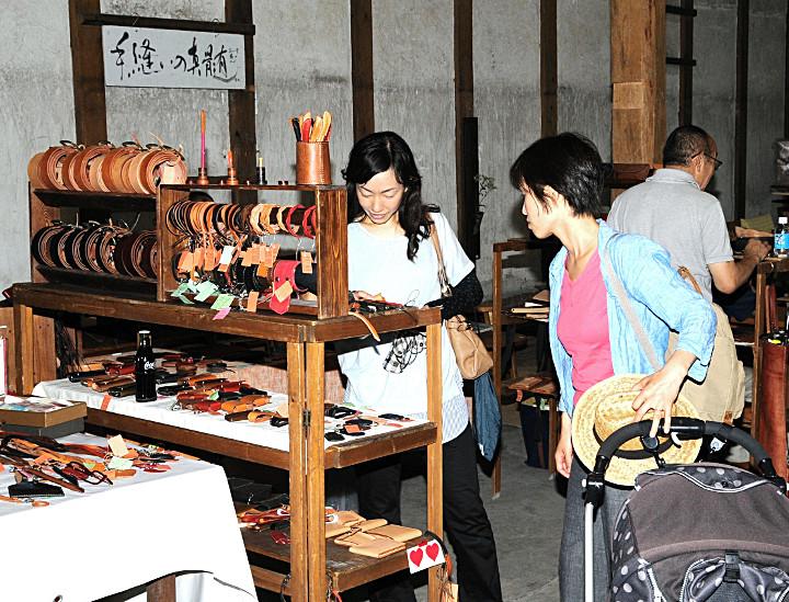 空き店舗を生かした会場で、革製品を見つめる来場者