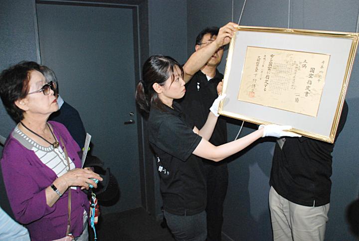 「仮面の女神」の国宝指定書を展示室に飾り付ける尖石縄文考古館職員