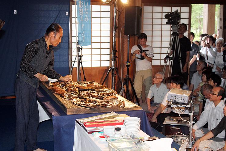 来場者に絵付けを披露する片岡さん(左)=井波別院瑞泉寺太子堂