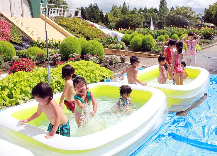 チューリップタワー前のプールで水遊びを楽しむ子どもたち=砺波チューリップ公園