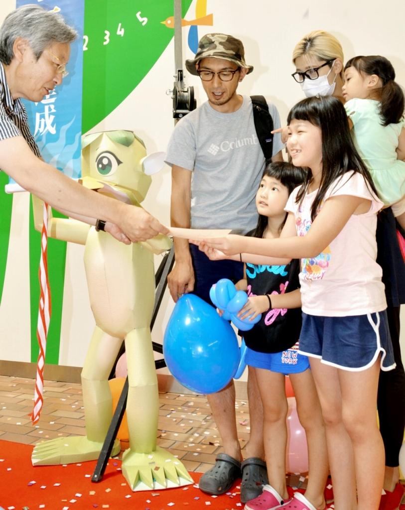 1万人目の入場者となり、笠松館長(左)から記念品を受け取る辻さん家族=23日、福井市の県立こども歴史文化館