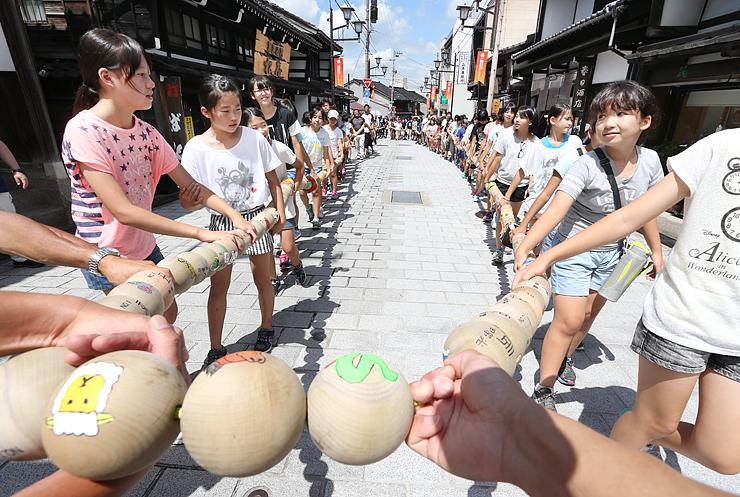 木球を数珠のようにつないだ大きな輪を運ぶ児童ら=南砺市井波の八日町通り
