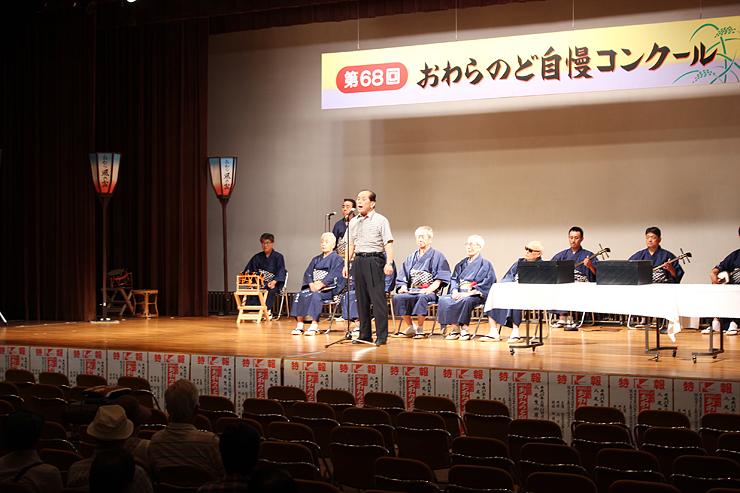 秀位1席に選ばれ、歌声を披露する中村さん(中央)=越中八尾観光会館