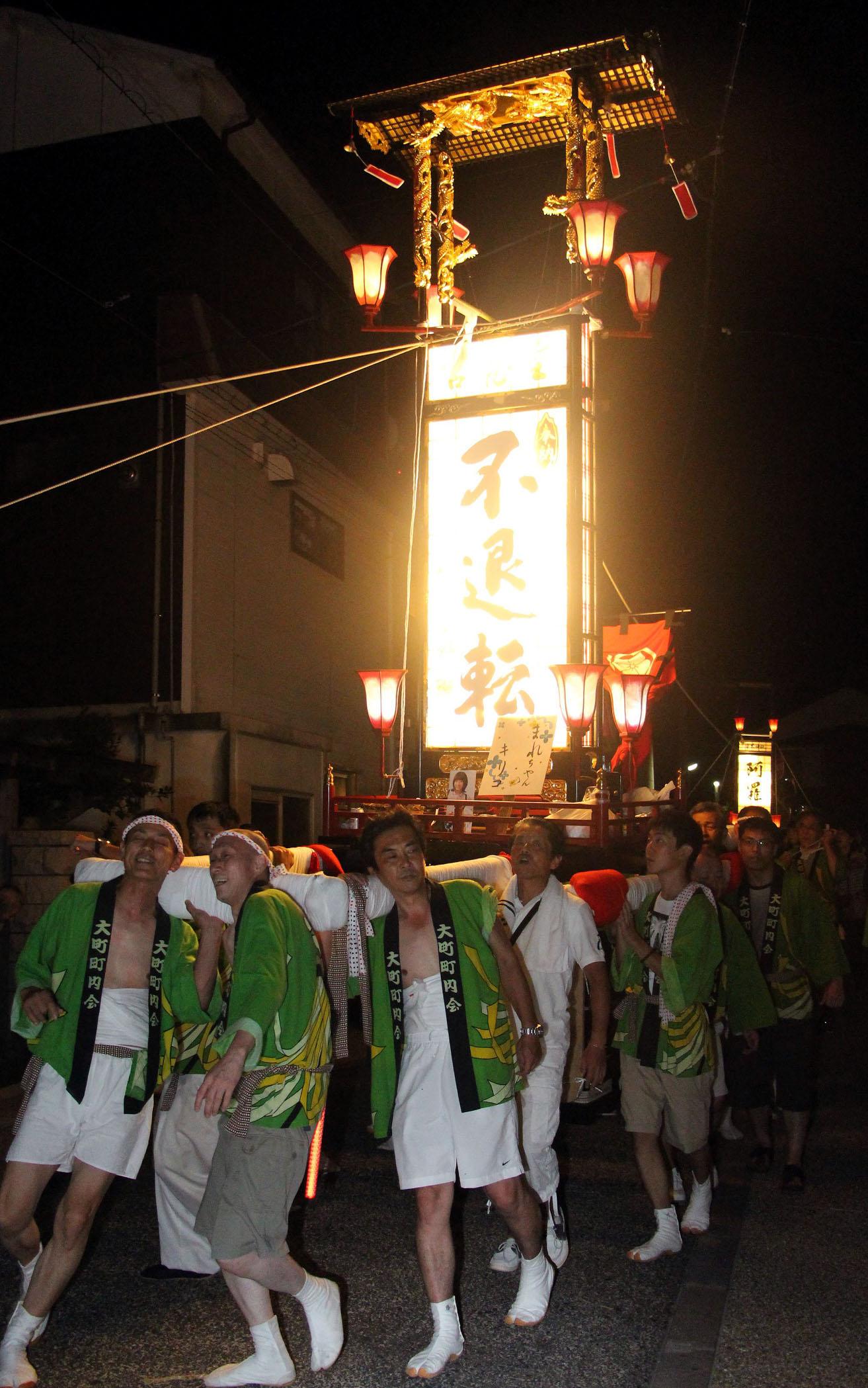 勇壮に町を練る「まれ」の撮影に使われたキリコ=23日午後10時、輪島市河井町