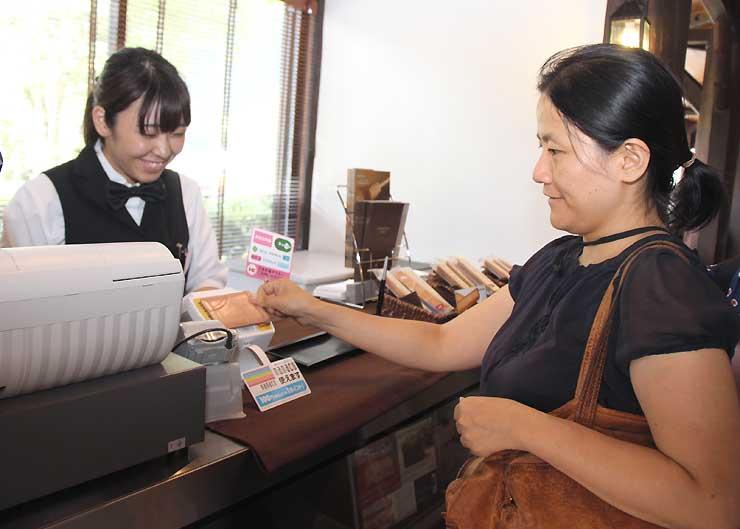 五千尺ホテルの喫茶室で、電子マネーで会計を済ませる女性客(右)