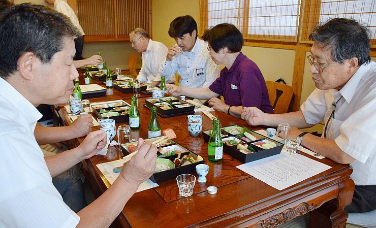 糸魚川の食材が詰まった弁当を試食する関係者=24日、糸魚川市