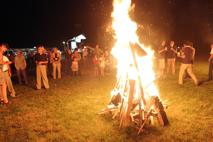 解体された彫刻が燃える様子を見つめる来場者=閑乗寺公園