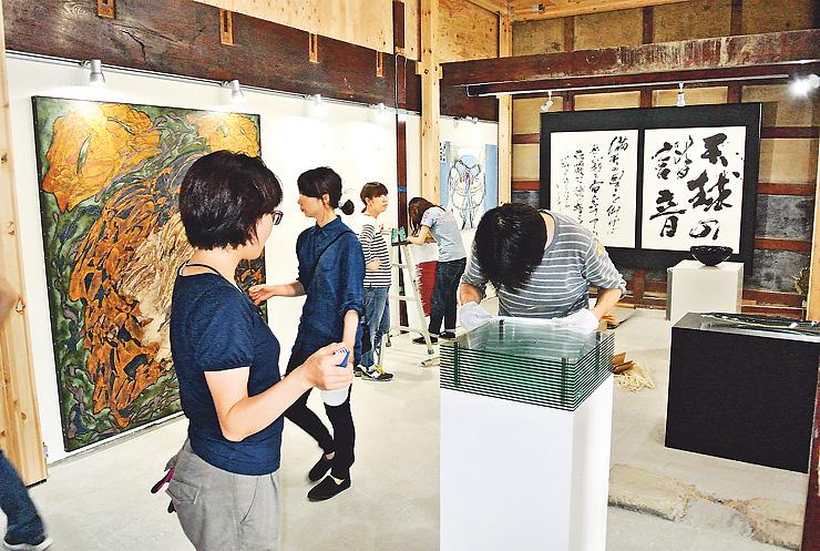 1日の開幕に向け、作品を展示する出品作家たち=富山市東岩瀬