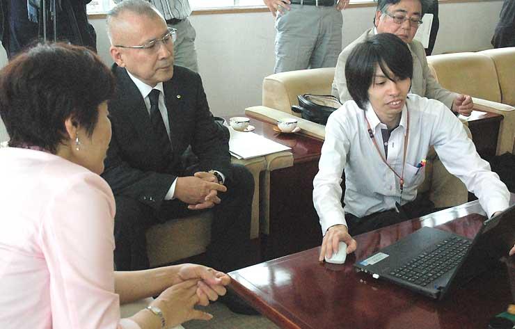 空き家バンクのインターネットサイトのデモ画面を見る金子市長(左)と茅野支部長(左から2人目)