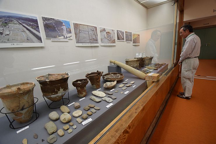 遺跡発掘調査で見つかった土器やヒスイなどが並ぶ企画展=糸魚川市