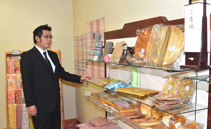 地元の工芸品が並ぶ売店の一角と村田支配人