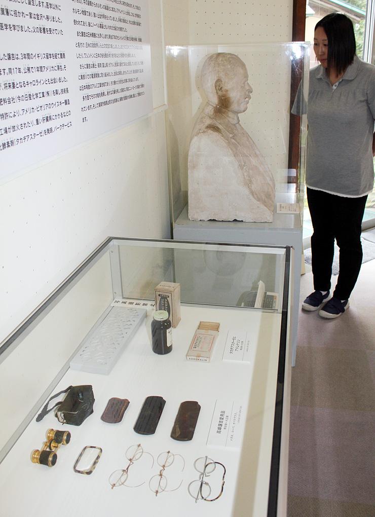 タカヂアスターゼの瓶や高峰博士の愛用品、胸像を展示している高岡市立博物館=同市古城