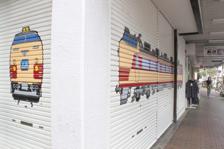 完成したばかりの特急北越クハなど鉄道アートがシャッターに描かれている新津新光商店街=3日、新潟市秋葉区