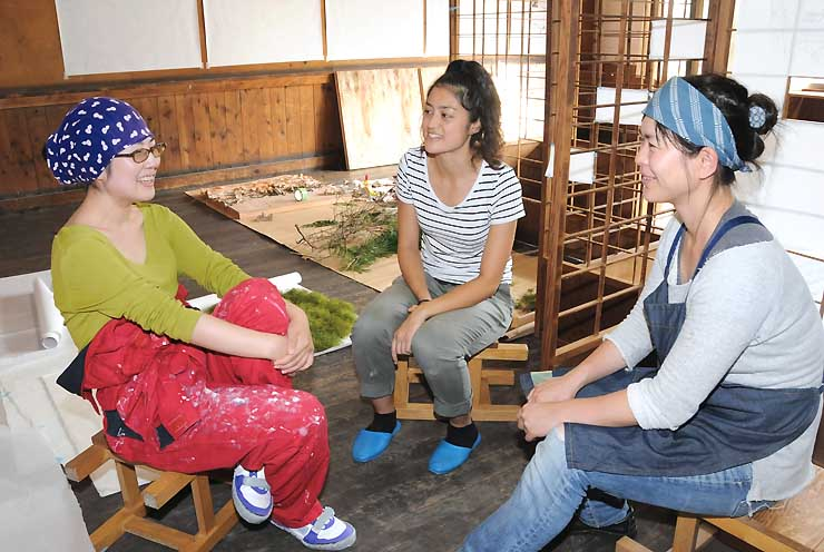 旧妻籠小の教室を使った伊藤さん(右)の制作現場で、美術展について打ち合わせる添野さん(左)、野口さん