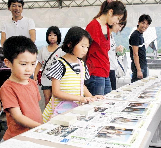 オリジナル新聞「マイ号外」を眺める家族=5日、福井県勝山市の福井県立恐竜博物館