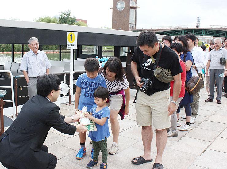 夏野次長(手前左)から記念品を受け取る朝陽ちゃんと家族ら
