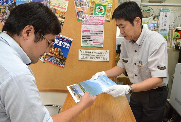 記念入場券が入った台紙を受け取る購入者(左)=安曇野市の豊科駅