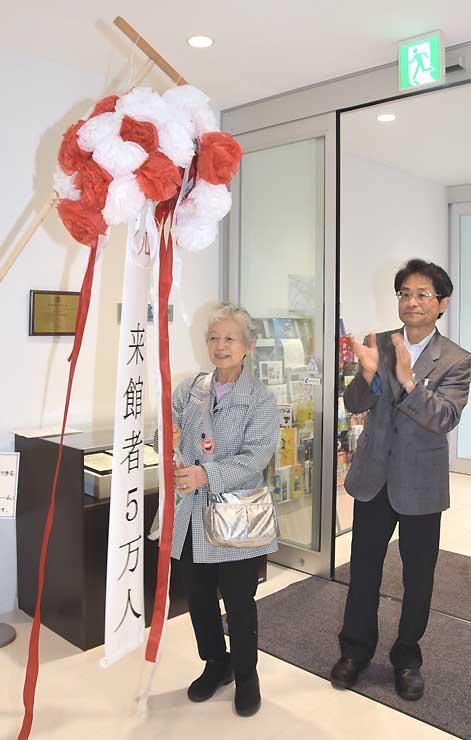 岡谷蚕糸博物館の5万人目の来館者となり、くす玉を割る竹内さん(中央)