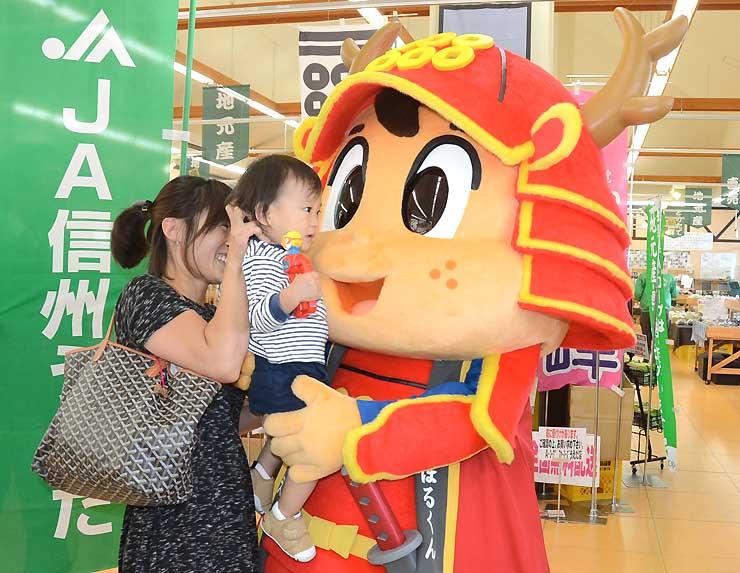 親子連れと触れ合うキャラクター「真田のぼるくん」=9日、上田市国分