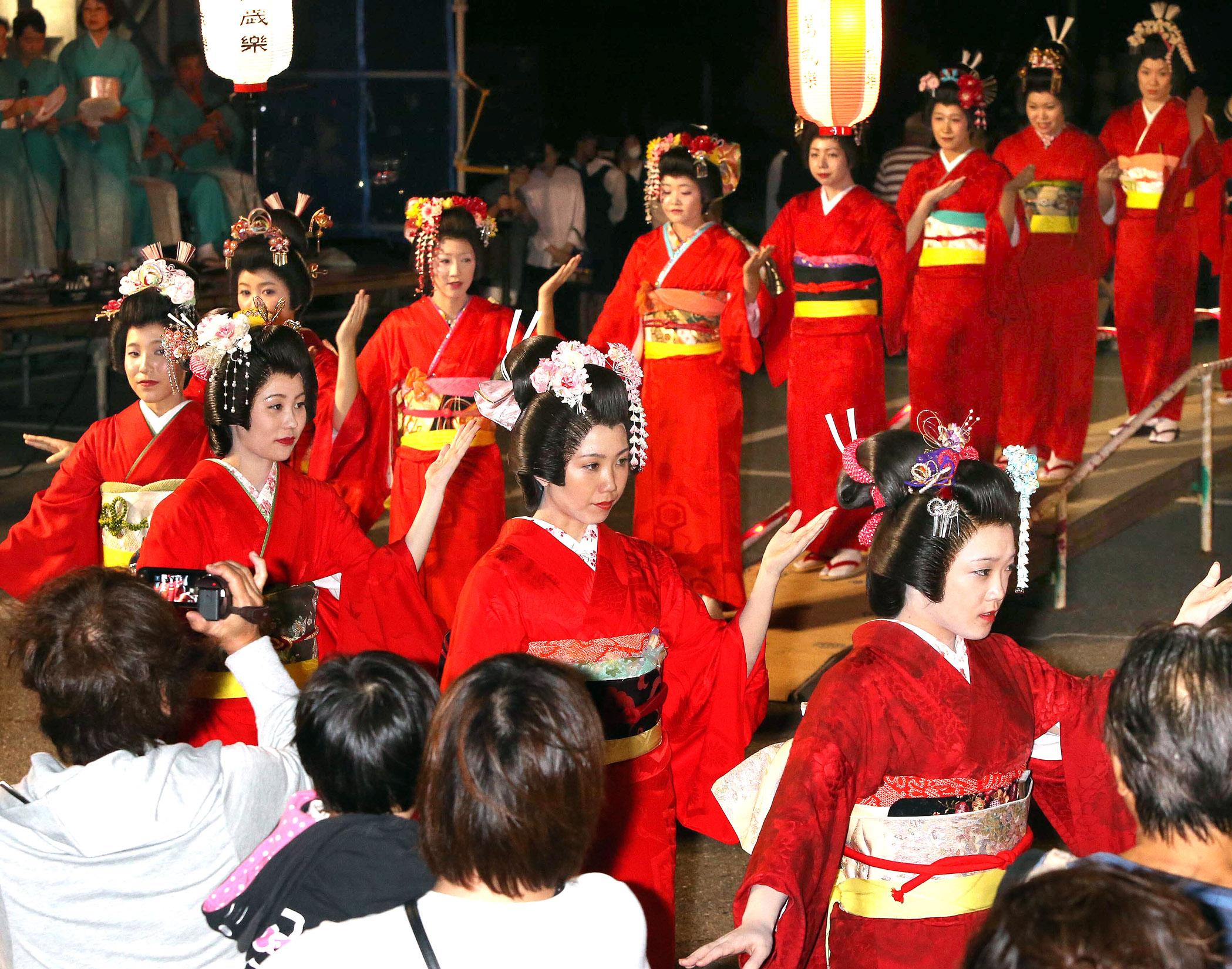 赤襦袢をまとい、あでやかな踊りを披露する踊り手=9日午後7時50分、小松市安宅町