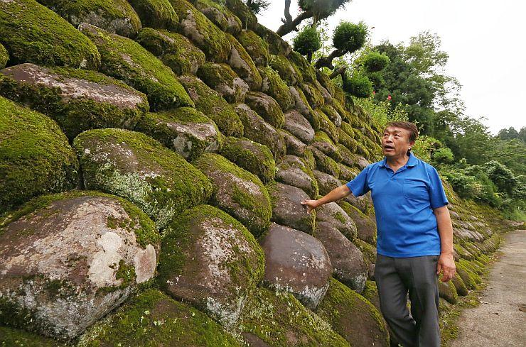丸みを帯びた石が整然と積み上げられた「ぼたもち石積み」。石積みの前で和栗俊一さんが解説する=上越市牧区