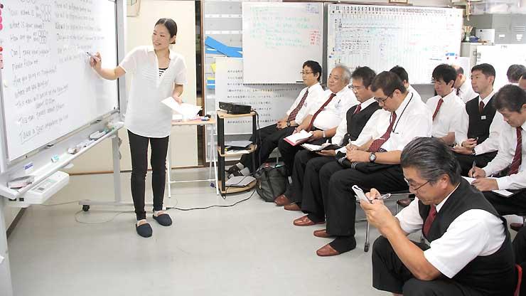 中央タクシー本社で、講師の女性から客とのやりとりに関する英会話を学ぶ乗務員=長野市