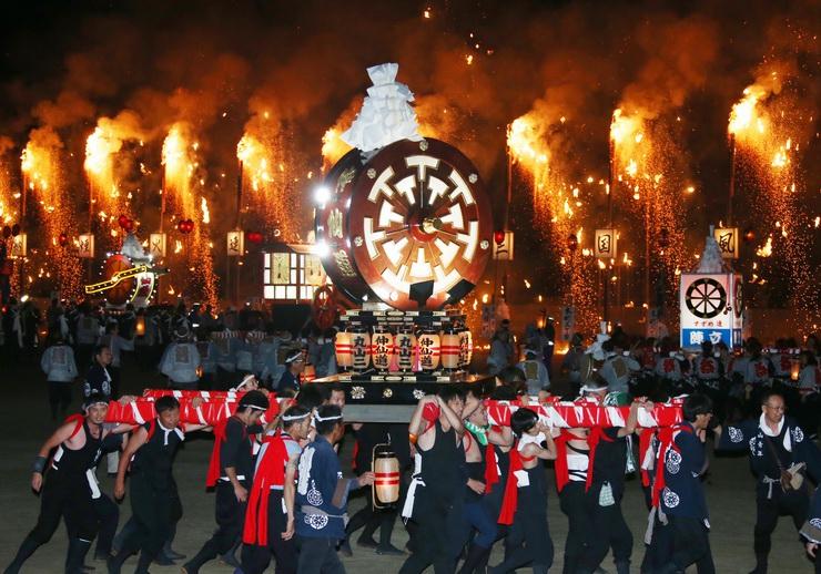 火の粉を降らす「連合大三国」の前で威勢良くみこしを担ぐ人たち