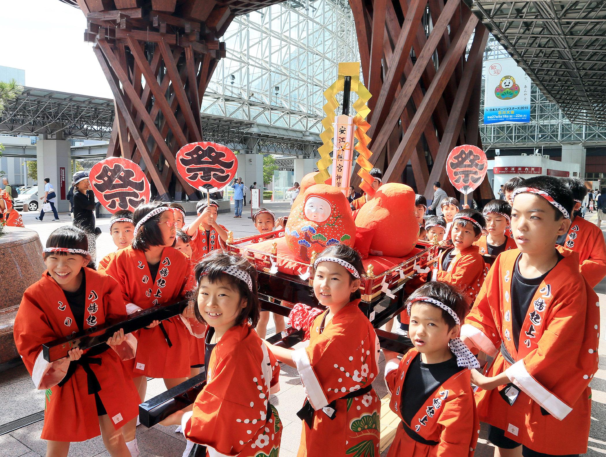 鼓門前で郷土玩具「加賀八幡起上り」を載せた神輿を元気よく担ぐ子どもたち=金沢駅