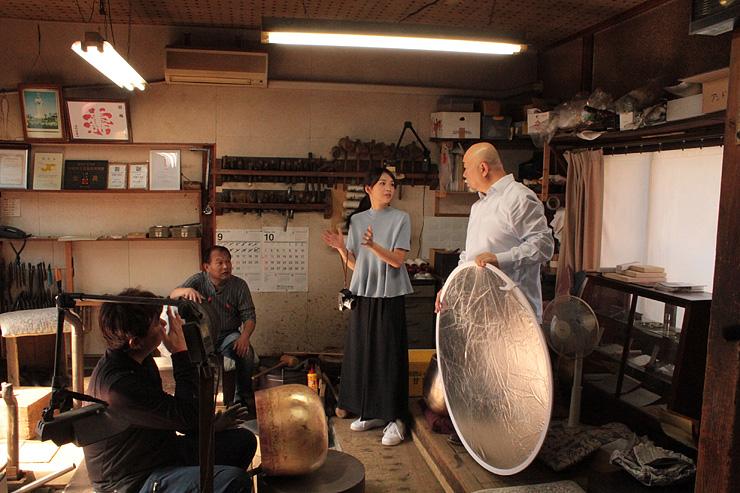 スタッフ(右)と打ち合わせながら島谷さん(左から2人目)と好徳さん(手前左)の撮影を進める舞川さん=シマタニ昇龍工房