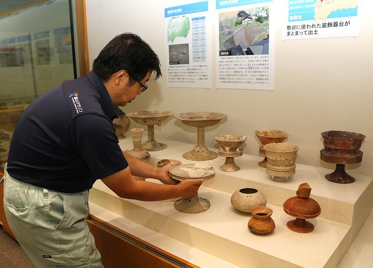 特別展に向け、急ピッチで準備作業を進める県埋蔵文化財センターの職員=同センター