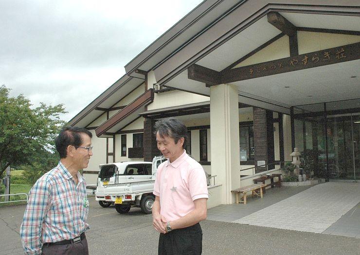 やすらぎ荘の前で談笑するファンクラブ会長の丸山公星さん(左)と古沢公男支配人=上越市板倉区