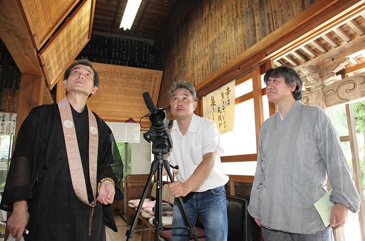 南砺市の寺院で移民ゆかりの史料を撮影する青原さん(中央)=2013年7月