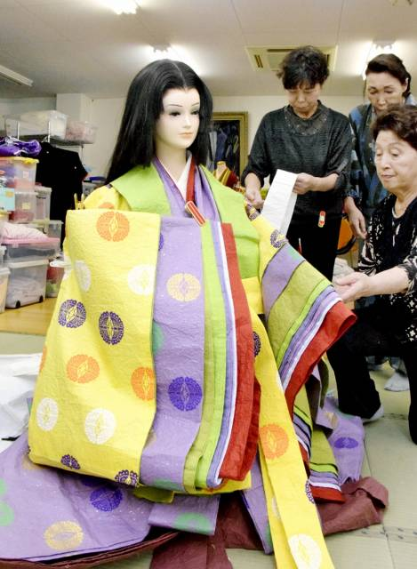 越前和紙による十二単姿の紫式部人形を制作する会員=18日、越前市府中1丁目